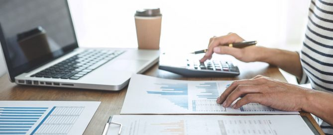 A-woman-double-checking-financial-report-using-calculator